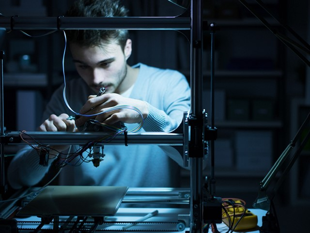 Engineer works with 3D printer in a darkened room