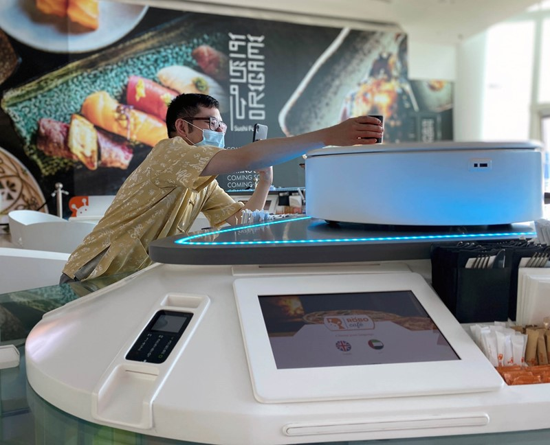A customer takes his drink which was prepared by a robot at a cafe in Dubai