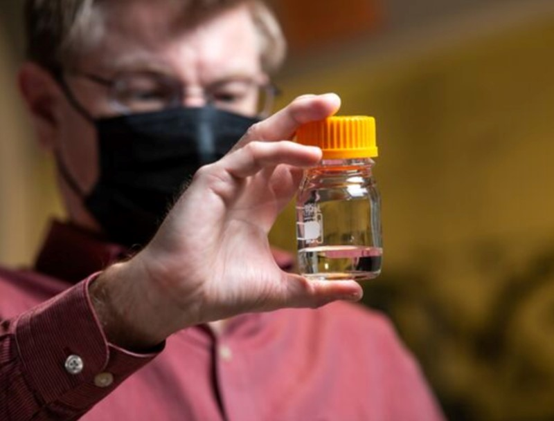 Robert Dagle holds a vial of fuel created from biomass conversion - inline